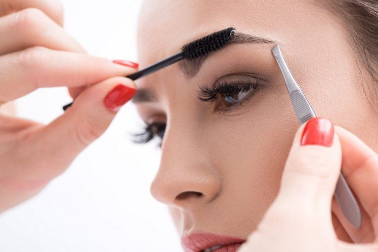 Young-woman-tweezing-her-eyebrows-in-beauty-saloon-768x513.jpg