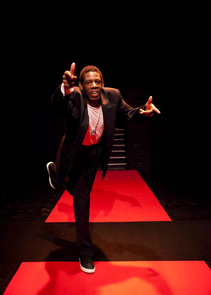 Photo credit: Rachel Cherry. Delson is a black man in his 30's, tall and average build. He is in a suit with a large silver bling chain. Delson is balancing confidently on a red carpet on one leg pointing directly into the camera.