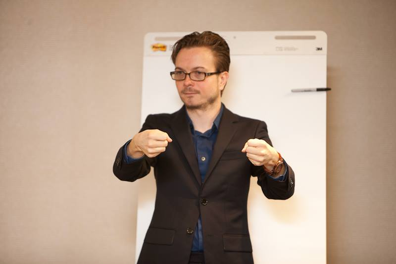 Wink standing in-front of a large paper writing board with both hands outstretched with closed fist. Wearing a brown suit and wearing brown glasses
