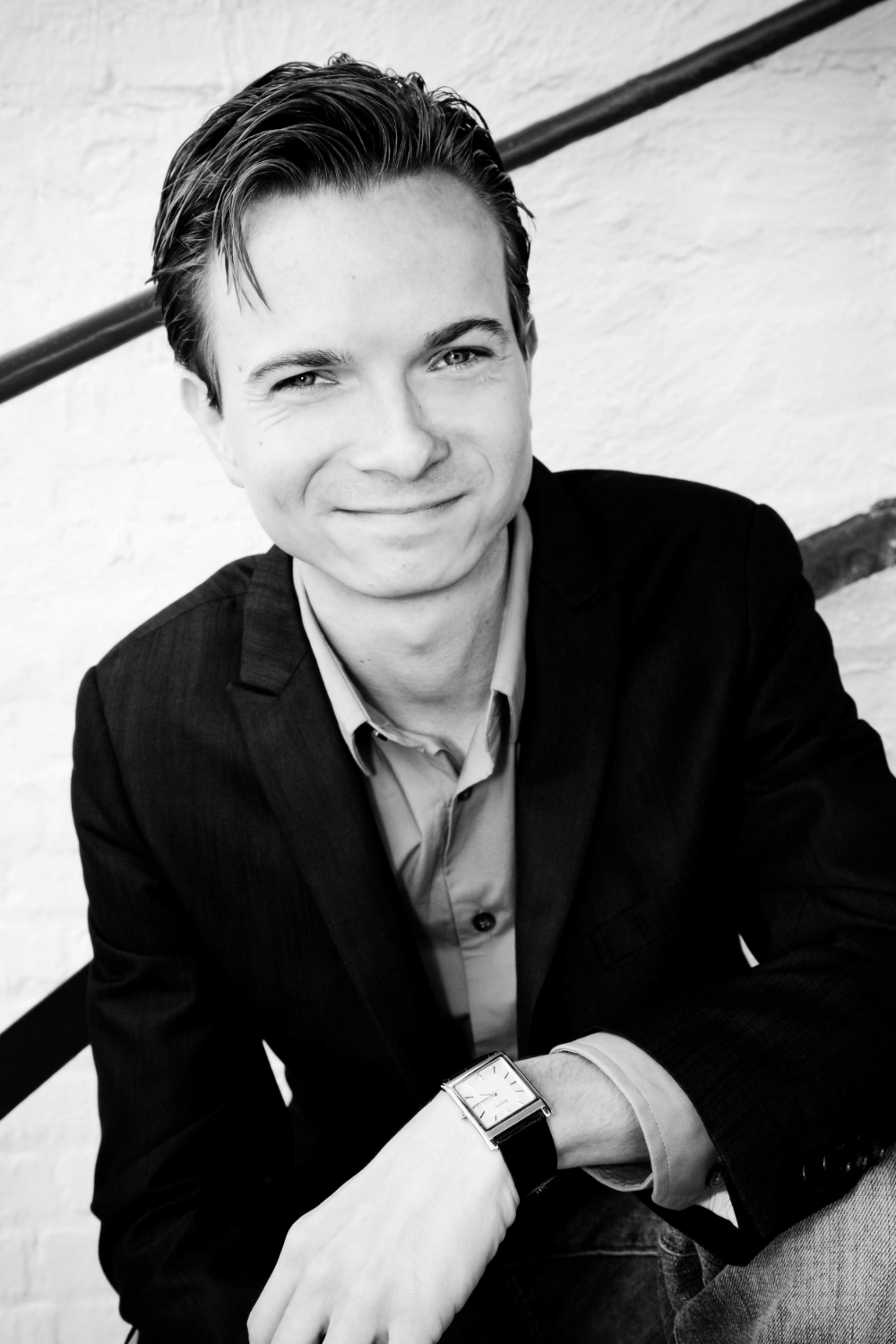 A black and white photo of Wink, a white man, clean shaven with hair parted to one side, not wearing glasses smiling at the camera while sitting in a stairwell and waring a suit, button up shirt, with no tie