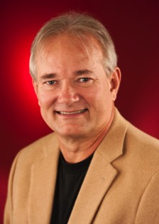 A color photo of Byron Bridges, a white man with grey hair, wearing a beige suit and black shirt smiling in-front of a red background.