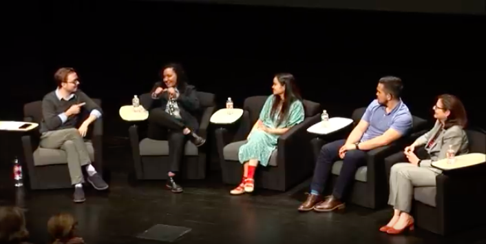 Wink sits stage right cross legged pointing at Reznet who is sitting to his left who is mid dialogue. Sitting next to Reznet is Claudia, not to her is Moises, and next to him is Dr. Padden