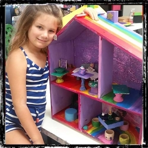 Very proud of her handcrafted dollhouse.