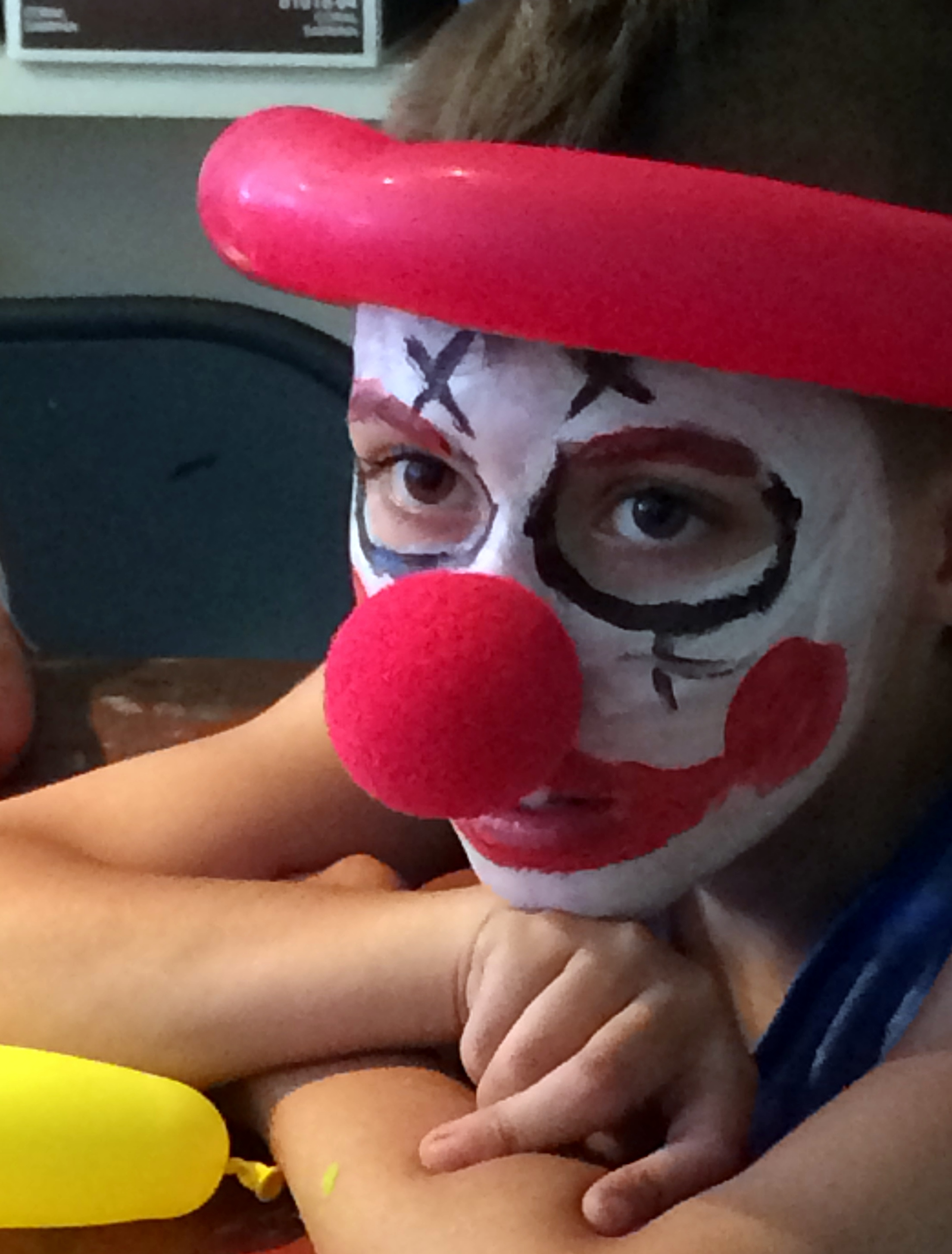 Face paint, balloon hat and clown nose.
