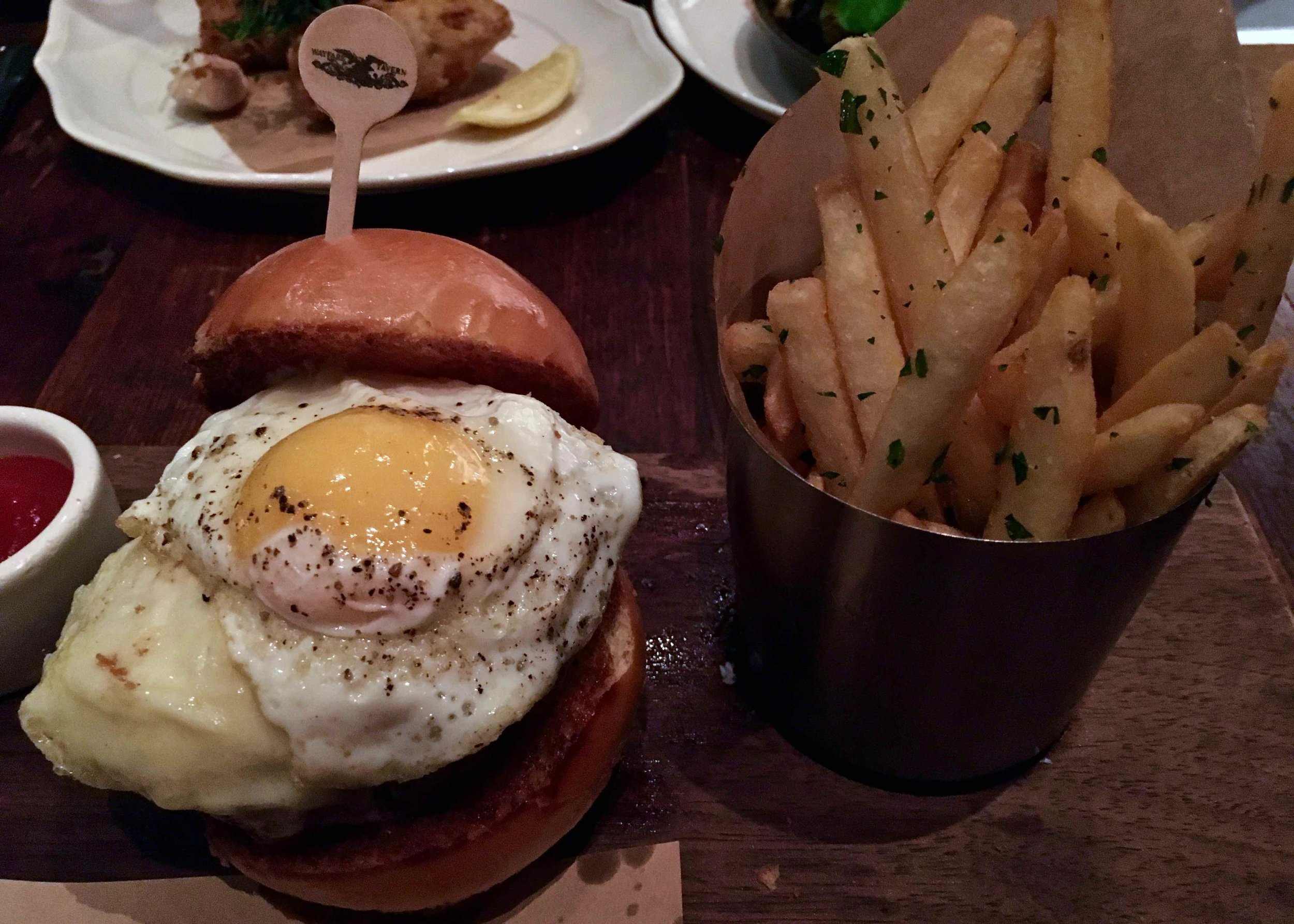 the tavern burger and fries with a fried egg
