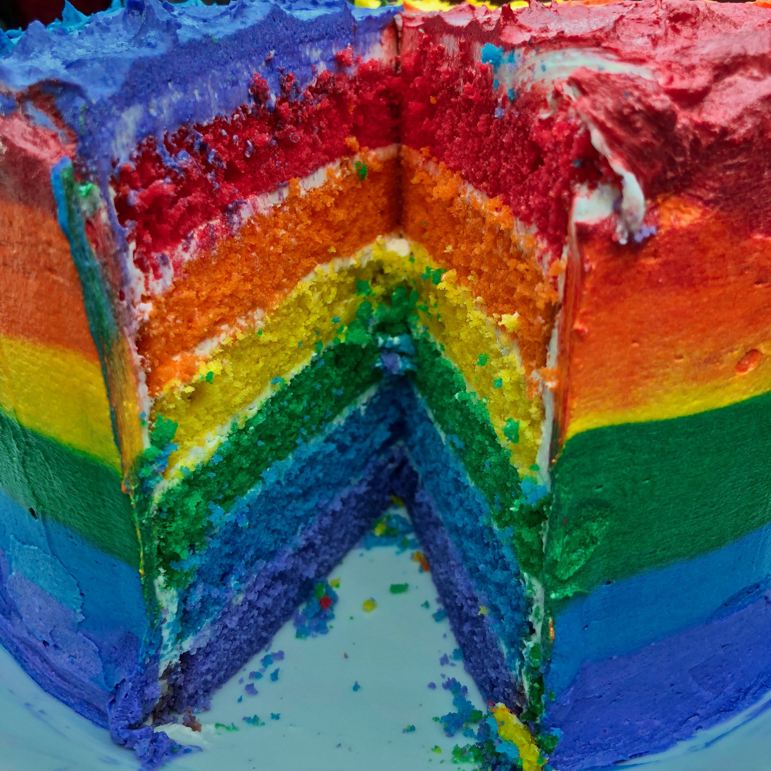 inside a rainbow frosted rainbow cake