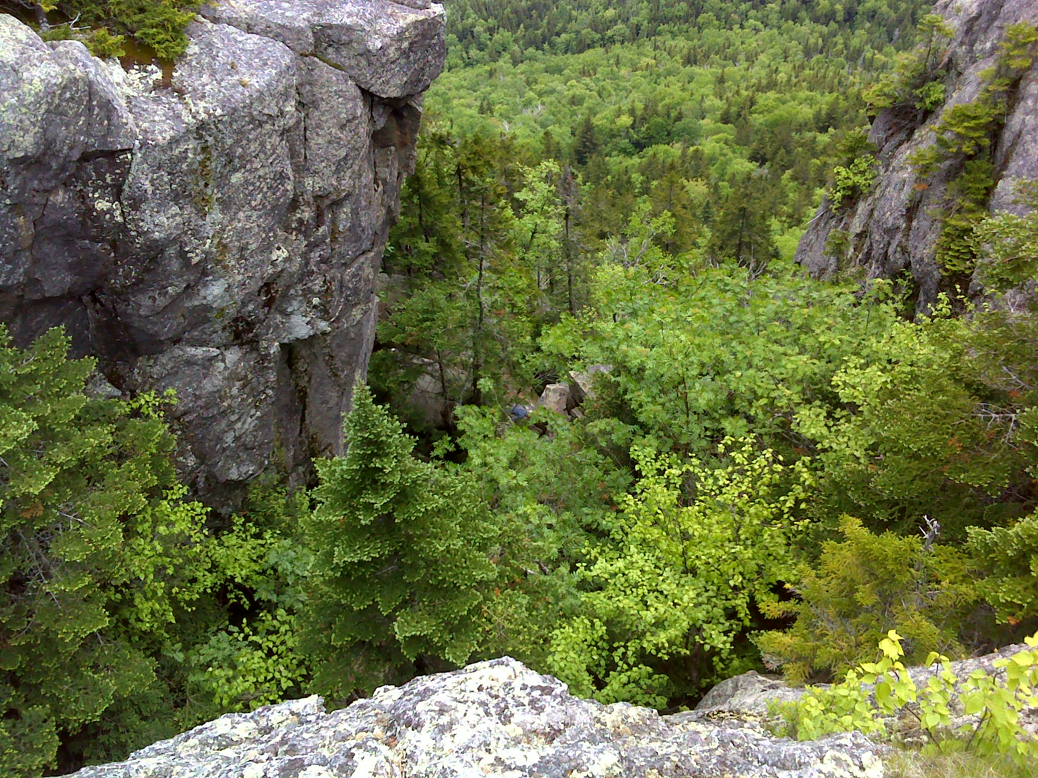 Looking down the chimney from the top. You can see a hiker standing on top of the boulder choke in the center of the frame