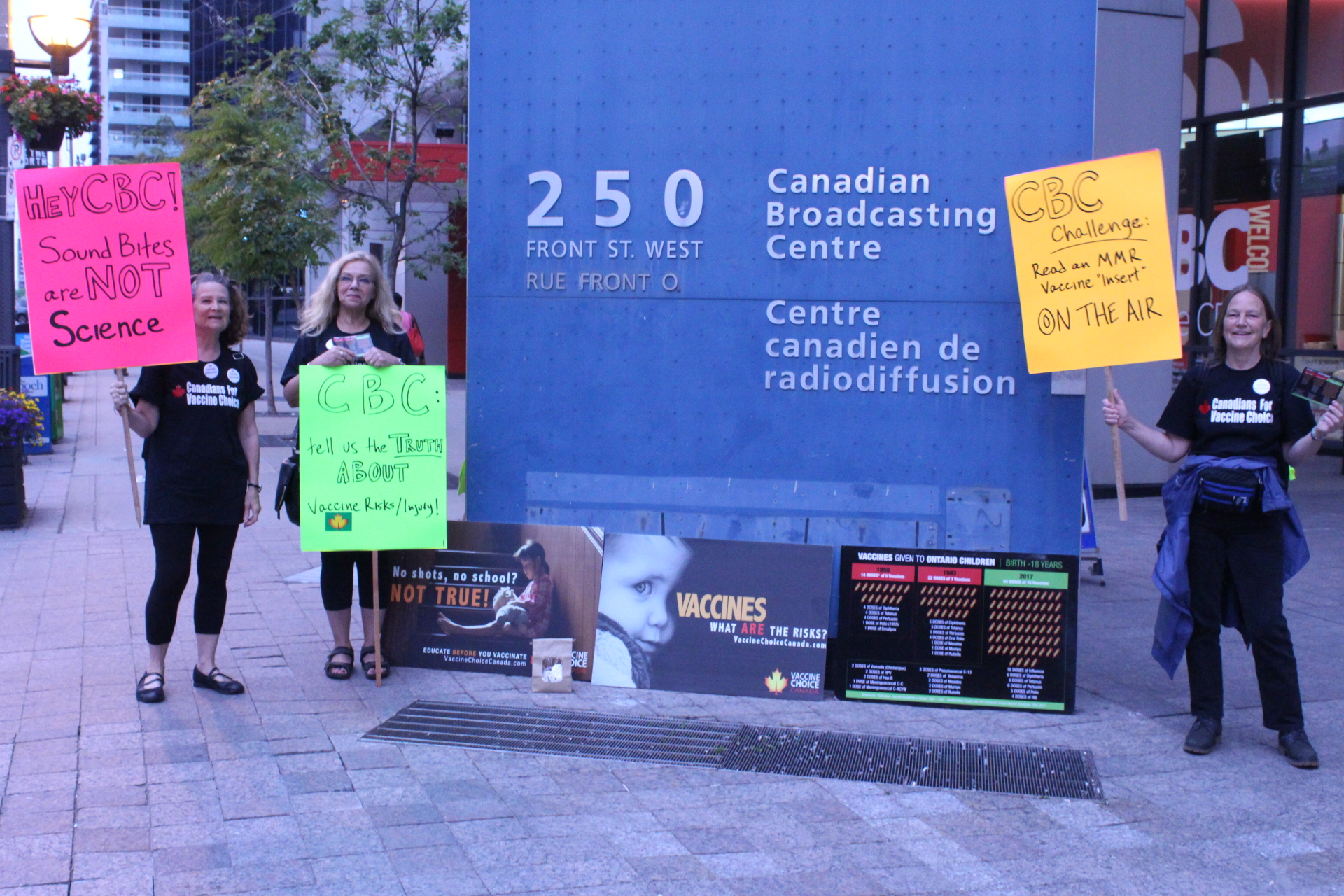 """Placards say, from left to right: Hey CBC. Sounds bites are not science; CBC: Tell us the truth about vaccine risks/injury; CBC Challenge: Read an MMR """"insert"""" on the air."""
