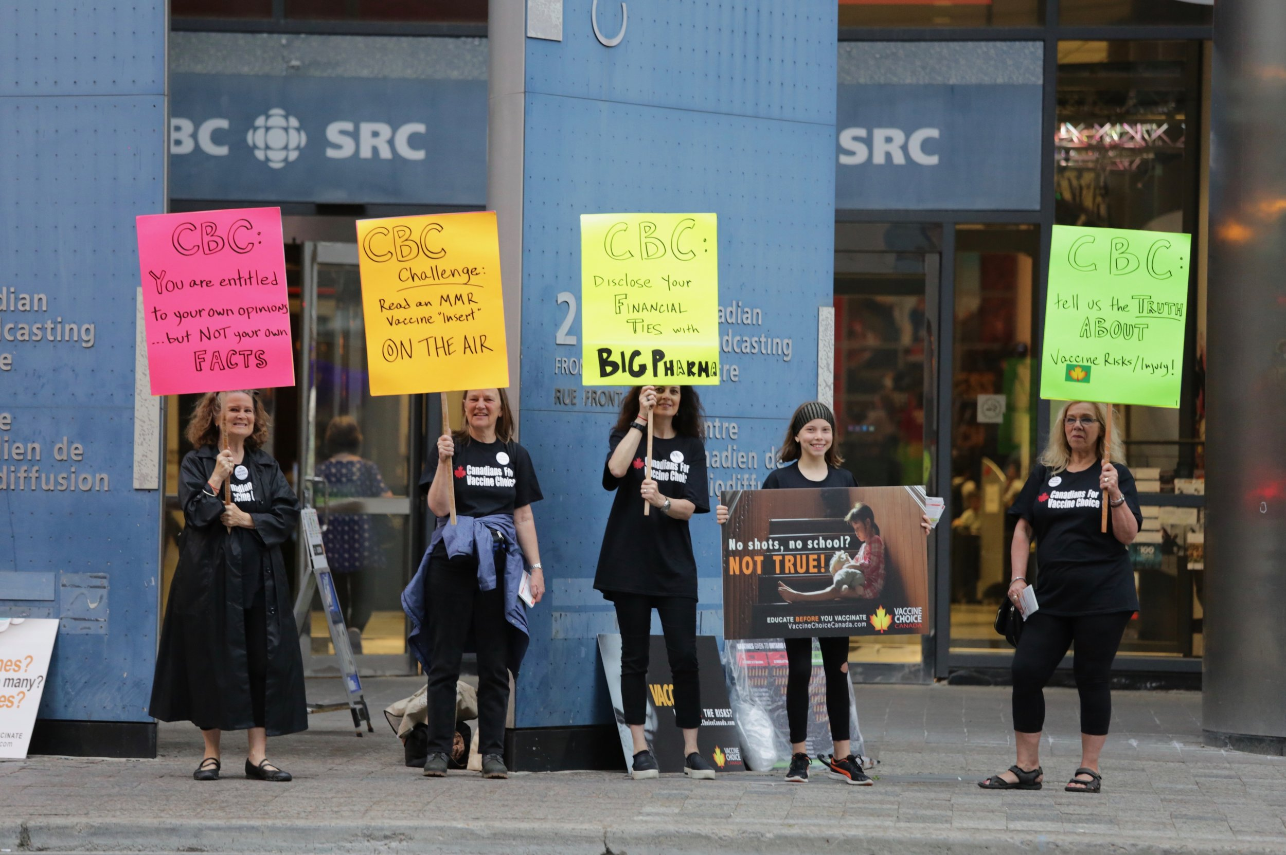 "The placards read, from left to right: CBC: You are entitled to your own opinions … but not your own facts; CBC Challenge: Read an MMR vaccine ""insert"" ON THE AIR; CBC: Disclose your financial ties with Big Pharma; No Shots, No School? NOT TRUE!; & CBC: Tell us the truth about vaccine risks/injury!"