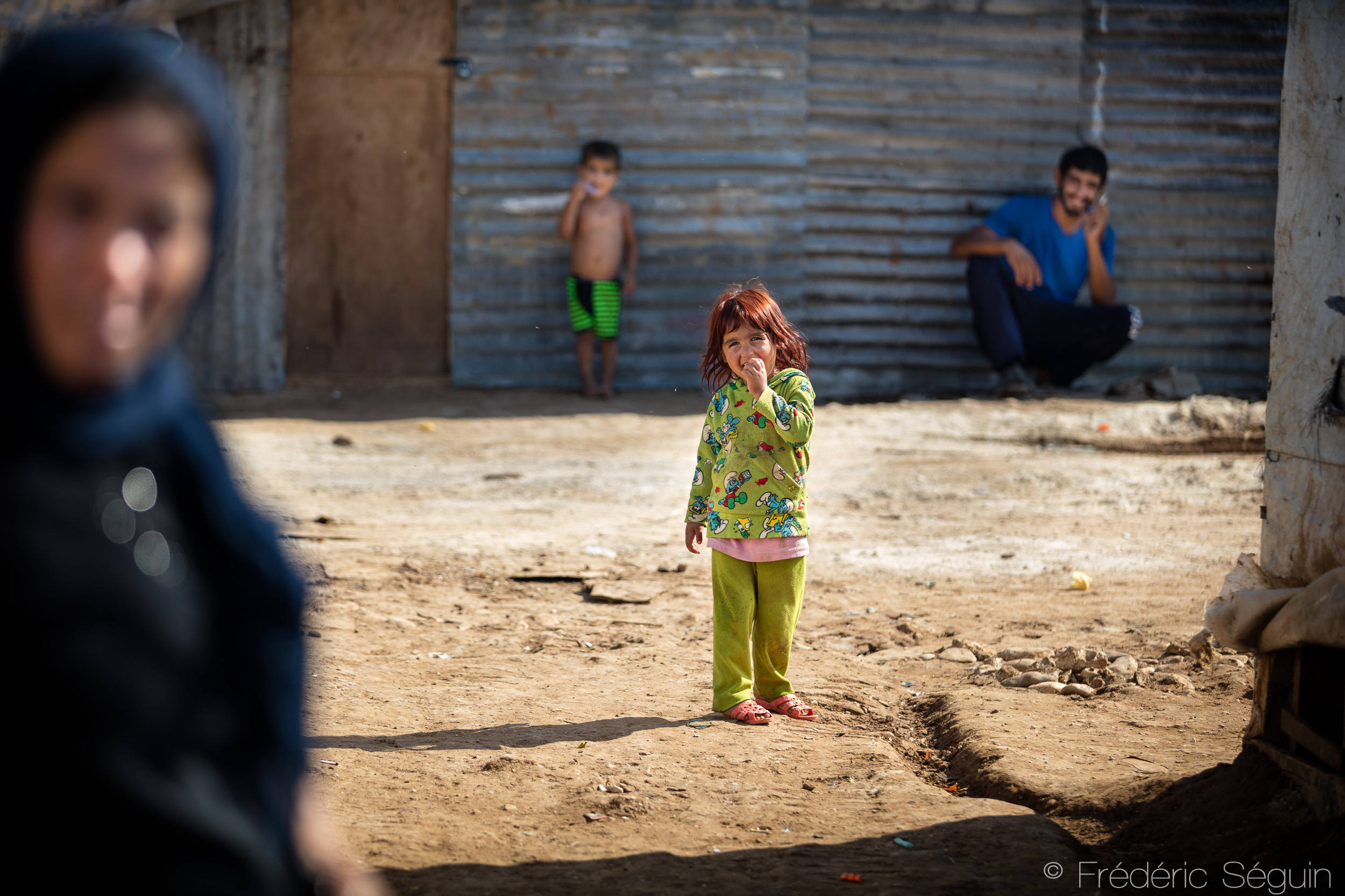 Among her relatives, a little girl smiles at the camera. Around 20 families live in the camp that has been reestablished in this location for one year. Akkar District, Lebanon. Photo credit: Frédéric Séguin,  Lebanon- The Other Side of the Sea .