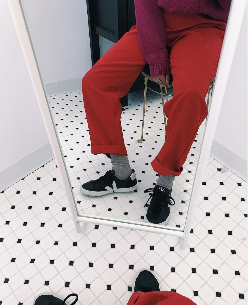 woman sitting on chair wearing veja sneakers and red pants