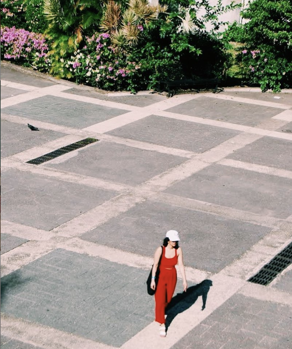 image of woman wearing all red with white hat walking