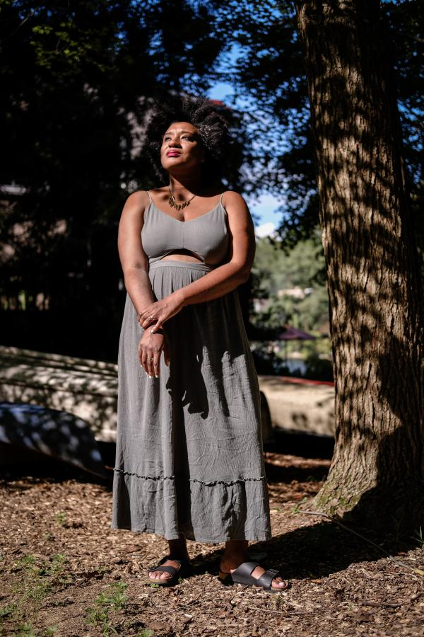 woman with natural hair and grey dress standing amongst trees