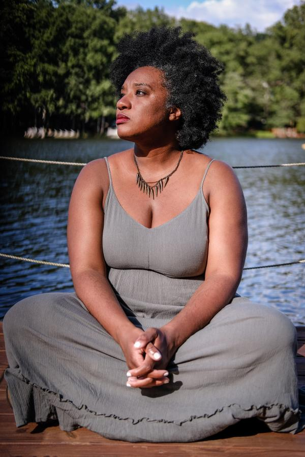 woman with natural hair and grey dress sitting cross legged in front of water and trees