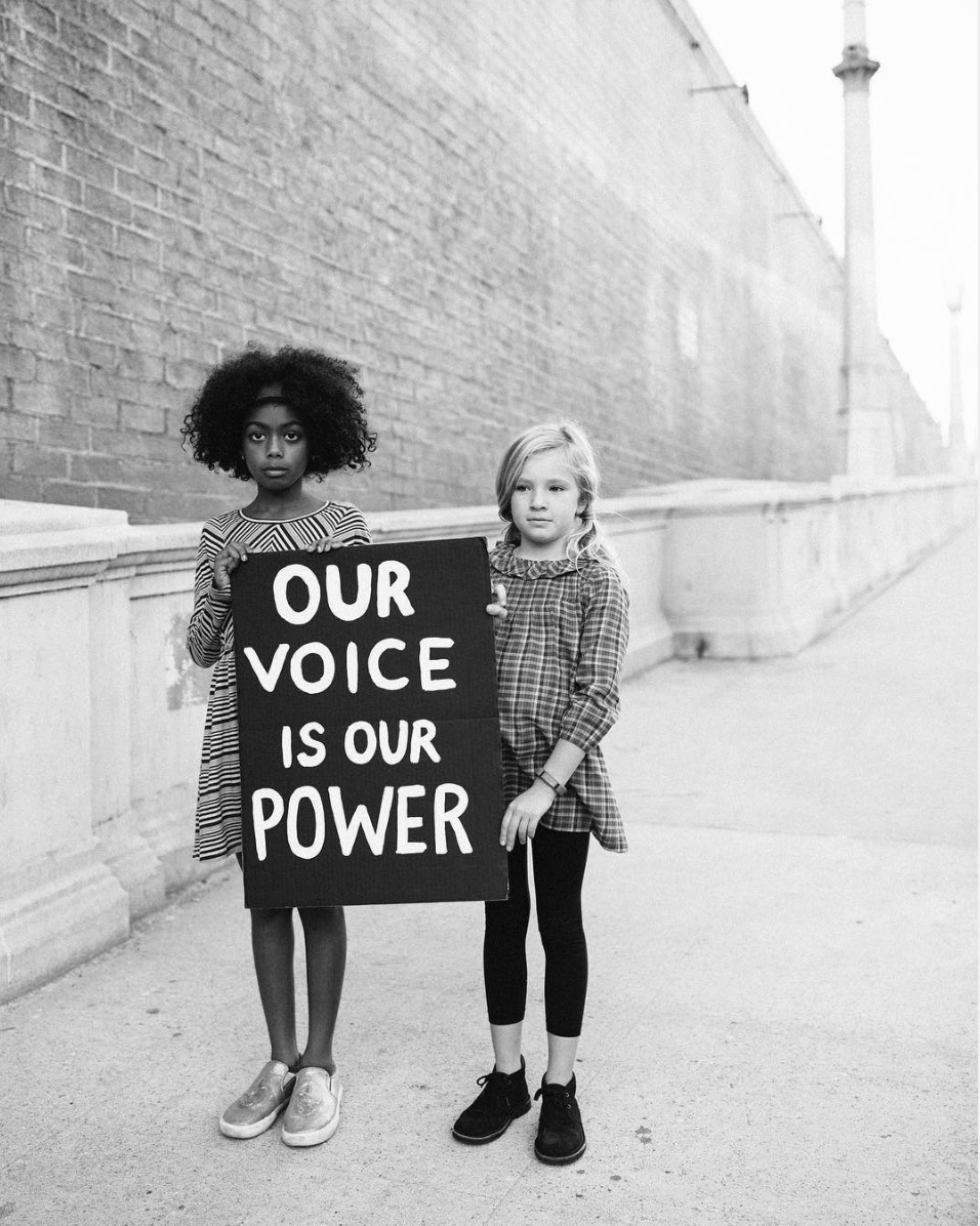 black and white image of two children holding sign that says our voice is our power