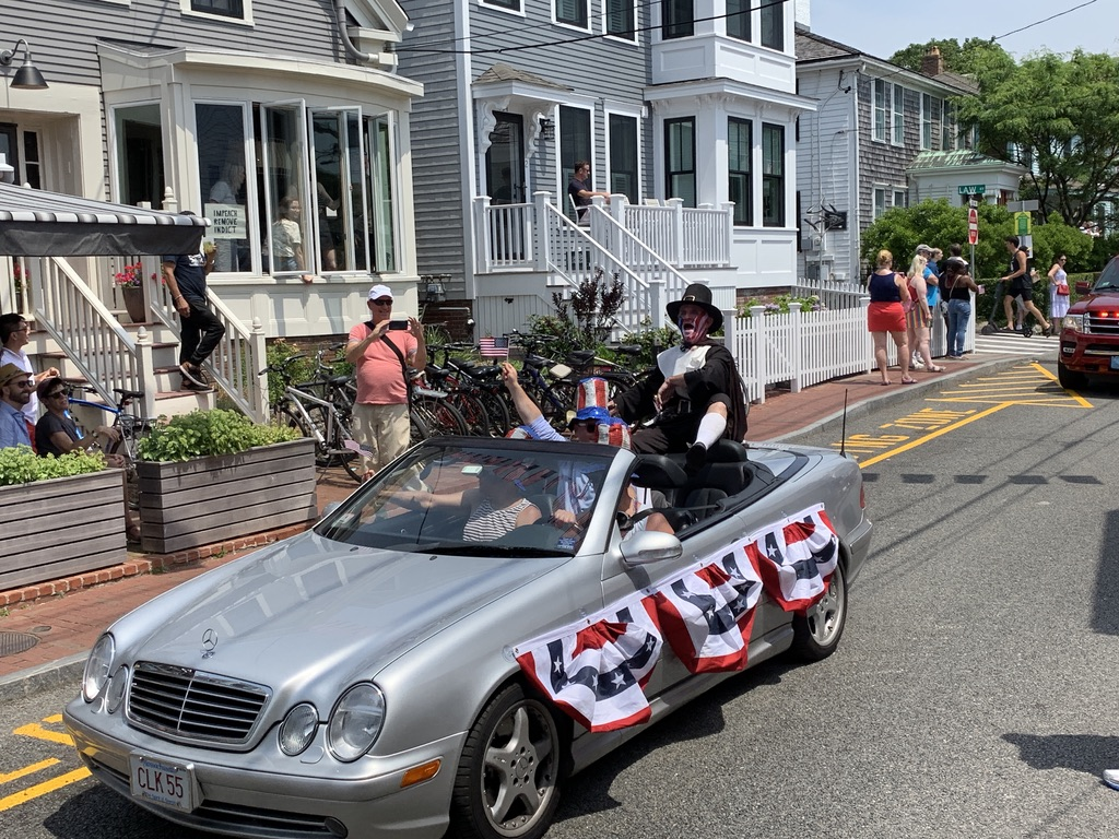 "The Town Crier during the July Fourth parade, still singing ""Grand Old Flag."" Note the sign in the window at left."
