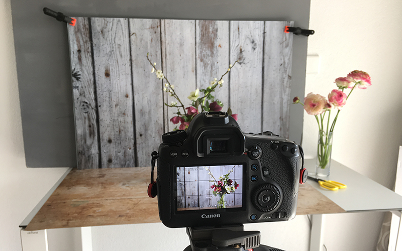 Table top setup with Lucy's light wood as a table top, and grey stone barn door as a backdrop