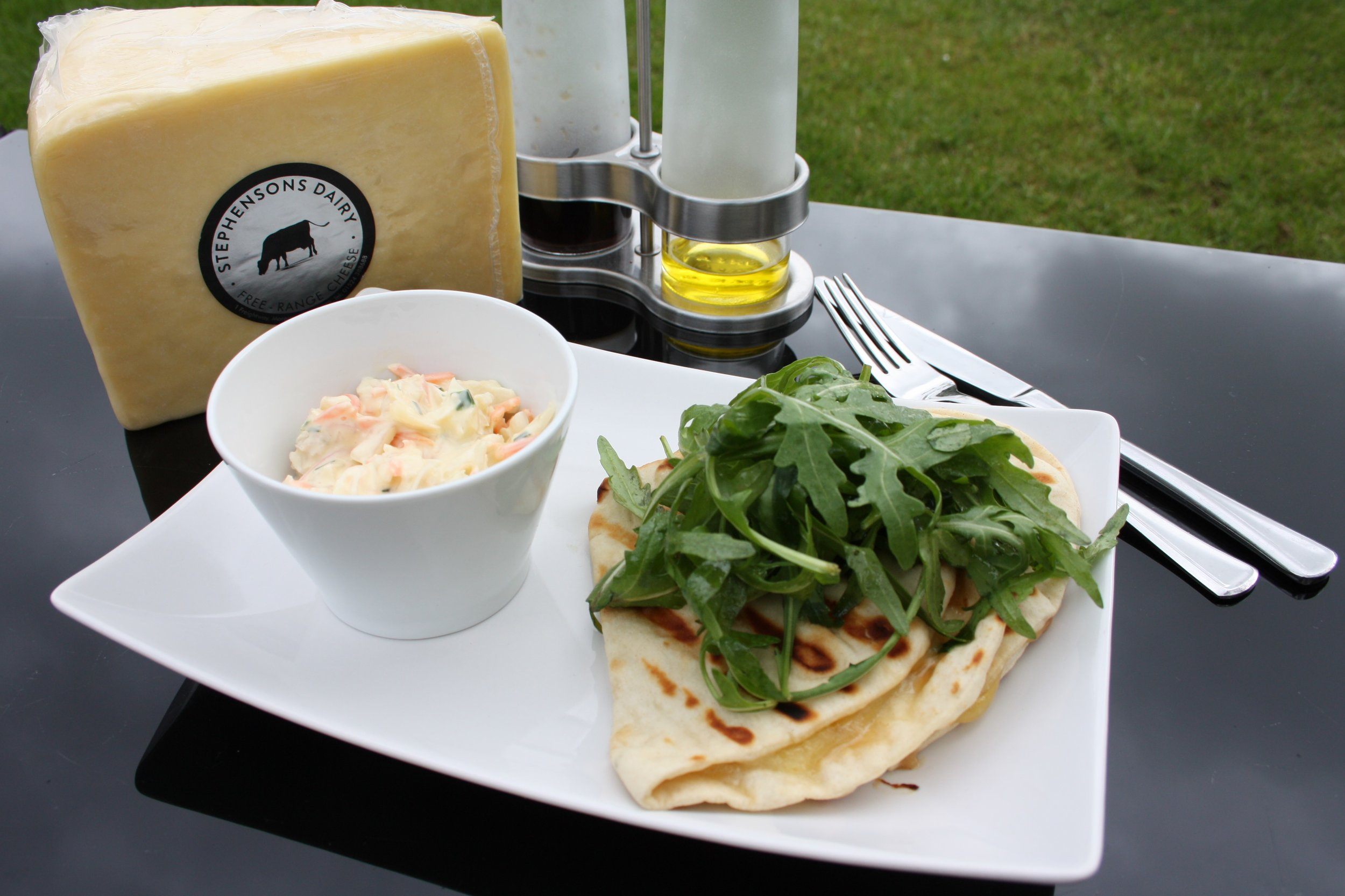 Grilled Lancashire Flatbreads - Serves 4200g Stephensons Free Range Lancashire Cheese4 flatbreads (can be gluten-free)8 teaspoons red onion chutney70 g rocket1 tbsp olive oil1 tbsp balsamic vinegarColeslaw, to serve (optional)Method1. Begin making the rocket salad. Pour the oil and vinegar into a large bowl and beat with a fork until thoroughly blended. Tip in the rocket and lightly mix together. Set aside.2. Slice the cheese thinly and place on one side of a flatbread. Spread the other side with 2 teaspoons of the chutney and fold in half. Repeat for the remaining 3 flatbreads. Grill in a panini maker or a lightly oiled frying pan until the cheese melts and the outside is lightly toasted.3. To serve, top the grilled flatbread with the rocket salad, and serve with a side of coleslaw.