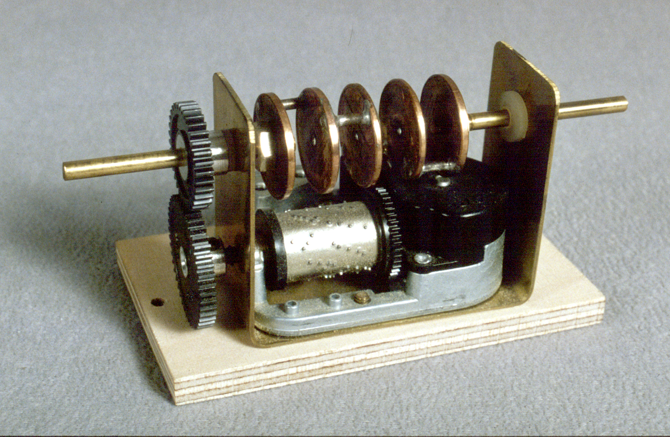 The controller prototype design is a stacked crankshaft made from pennies that has been silver soldered together and linked to a Sanyo music box movement with nylon gears used for slot cars.