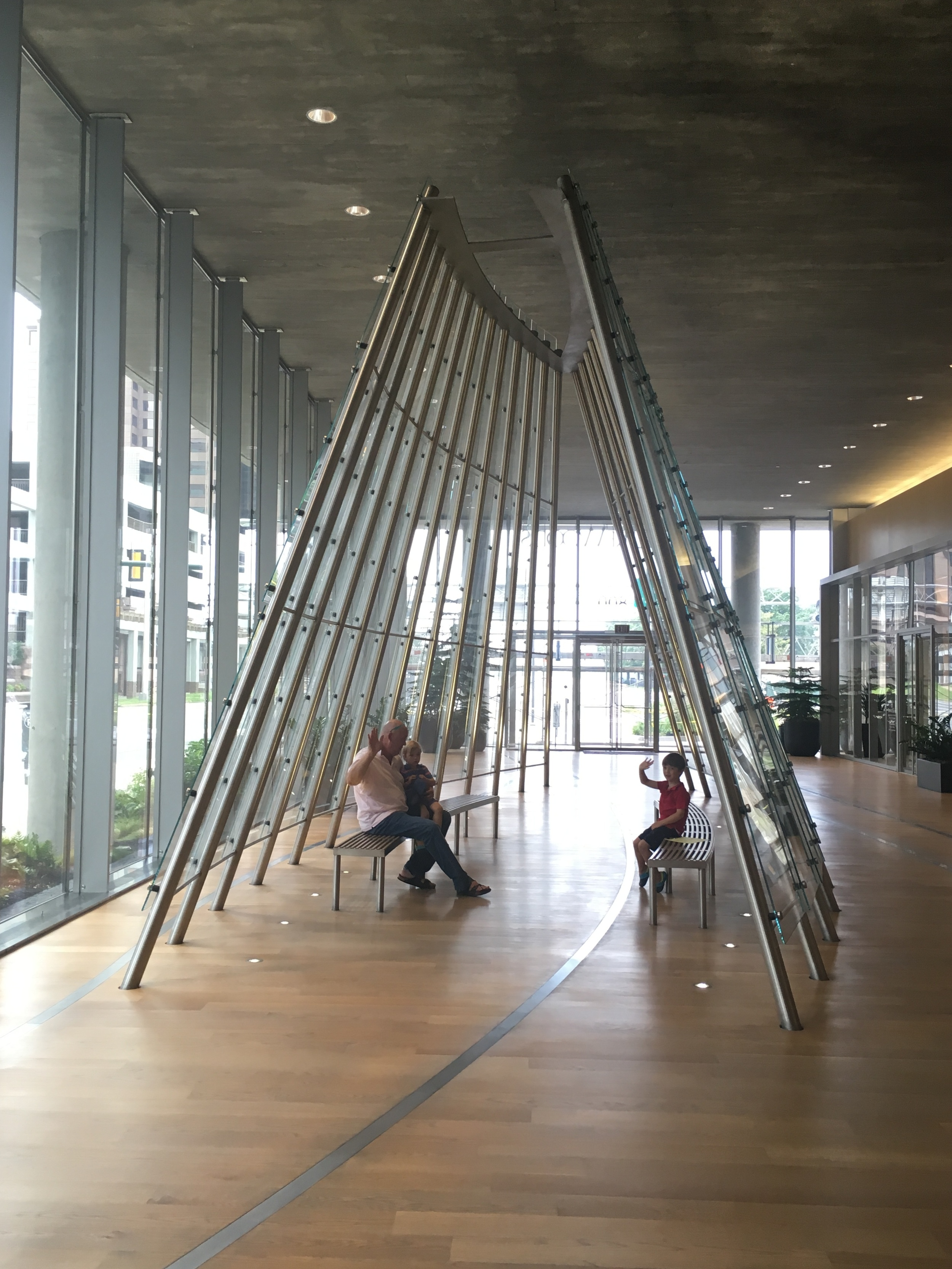 Hine family sitting and waving in  Clear Passage,  one of three elements of  Gateway Trio (2015)  in Clayco's Gateway Plaza building in Richmond, Virginia.  (Photo: Laure Tillinghast Hine)