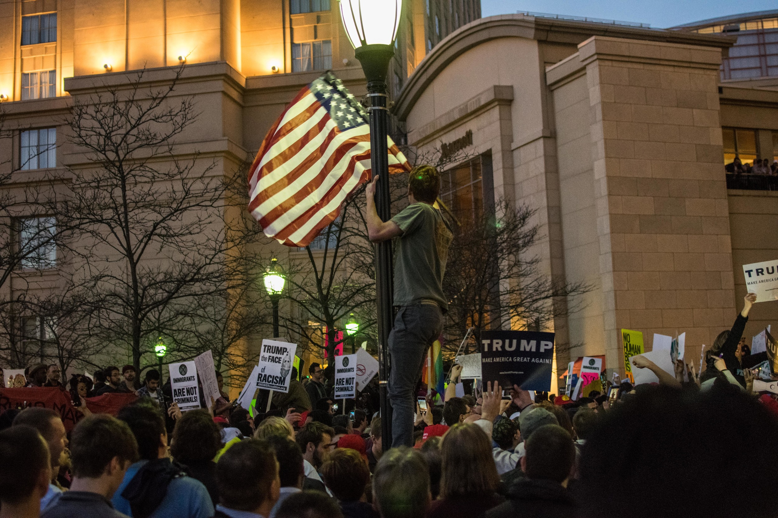 A Trump supporter emerges from the sea of people, hanging from a lamppost and wielding an American flag.