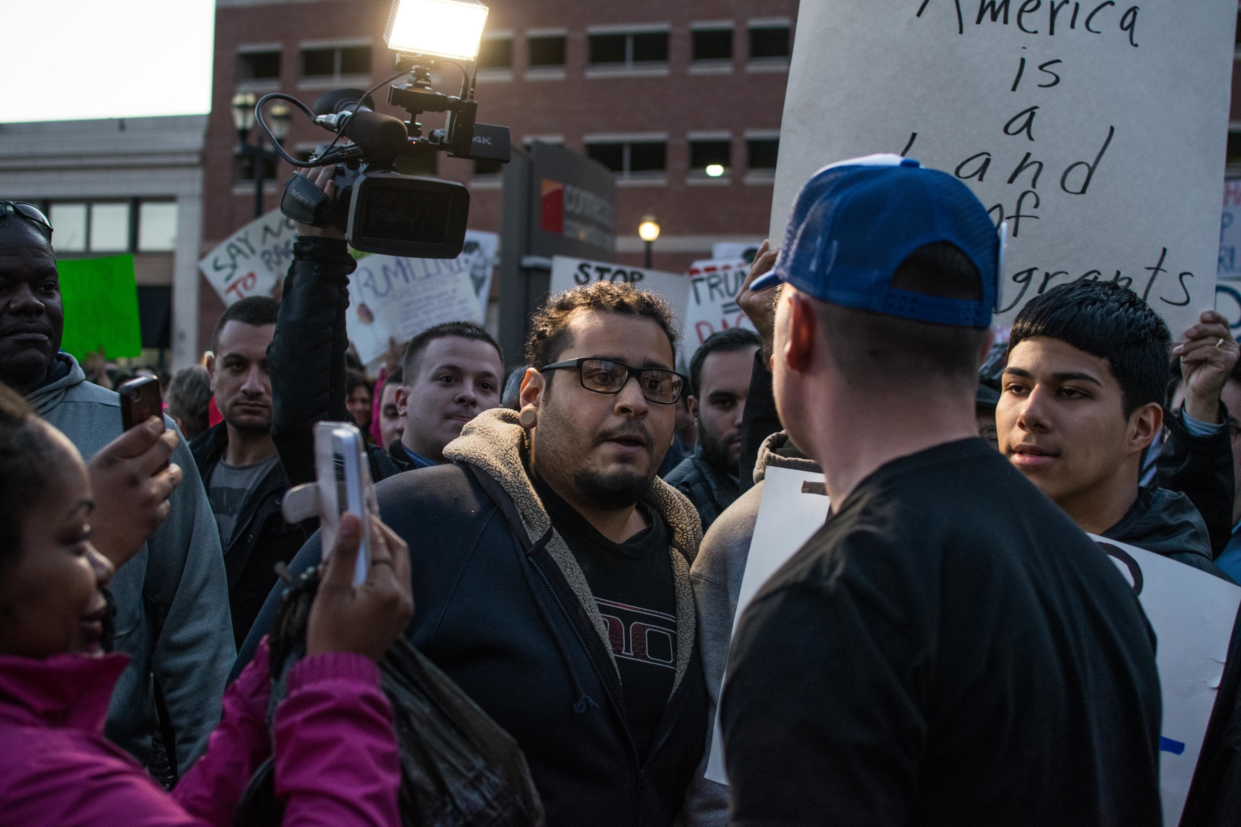 A Trump supporter (in the blue hat) confronts a group of protestors.