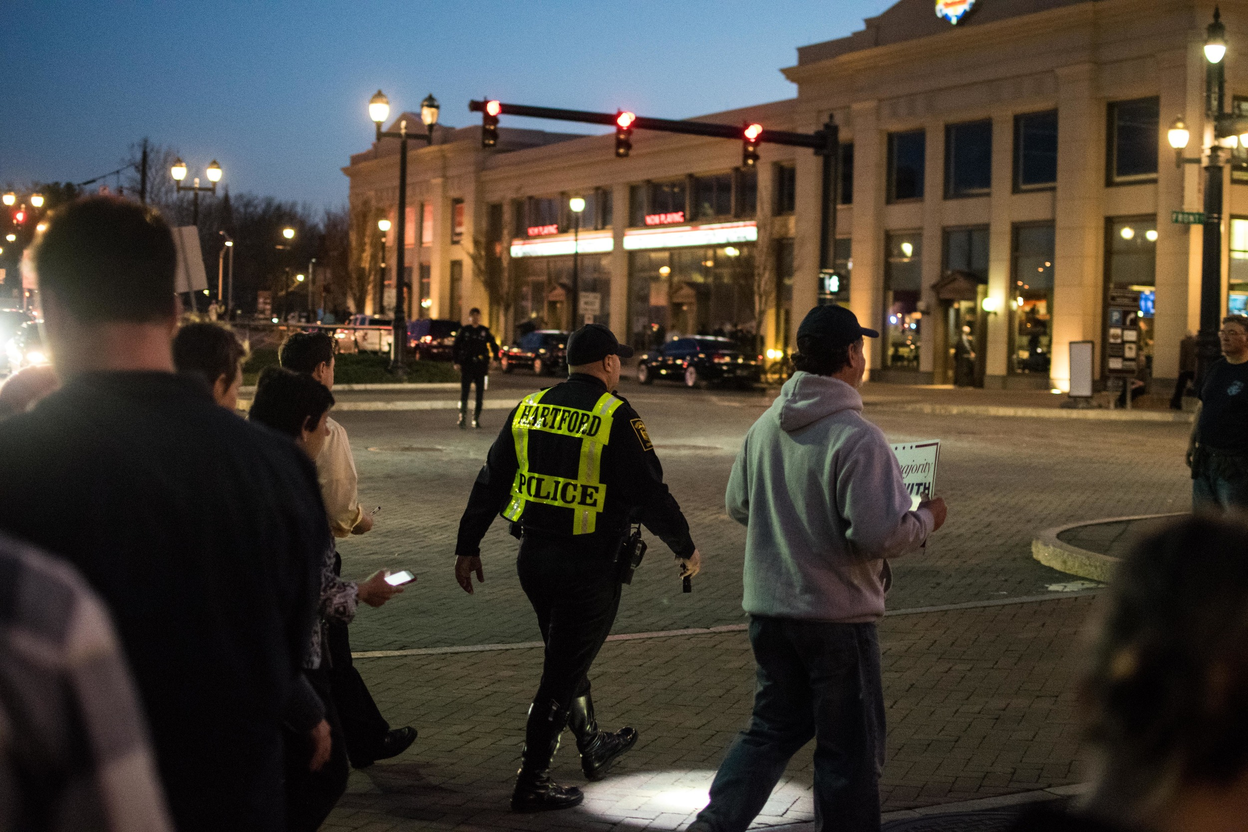 A police officer guides a large crowd across a busy street.