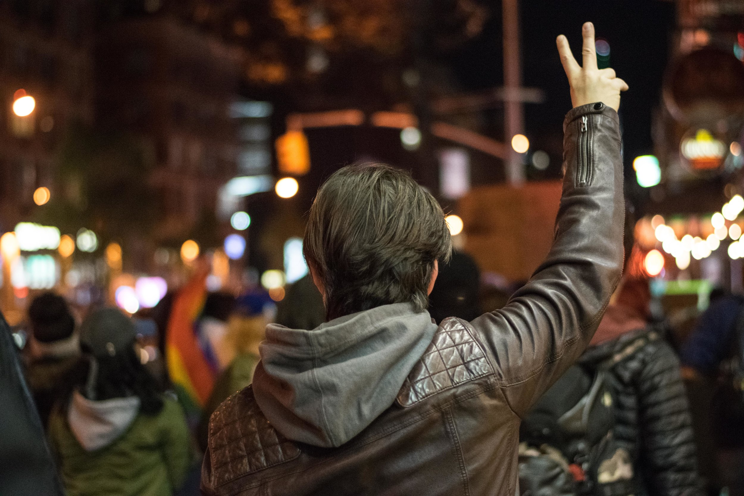 2016-NYC-New-York-Trump-Protest-March-Man-White-With-Leather-jacket-arm-held-up-fingers-hand-peace-sign