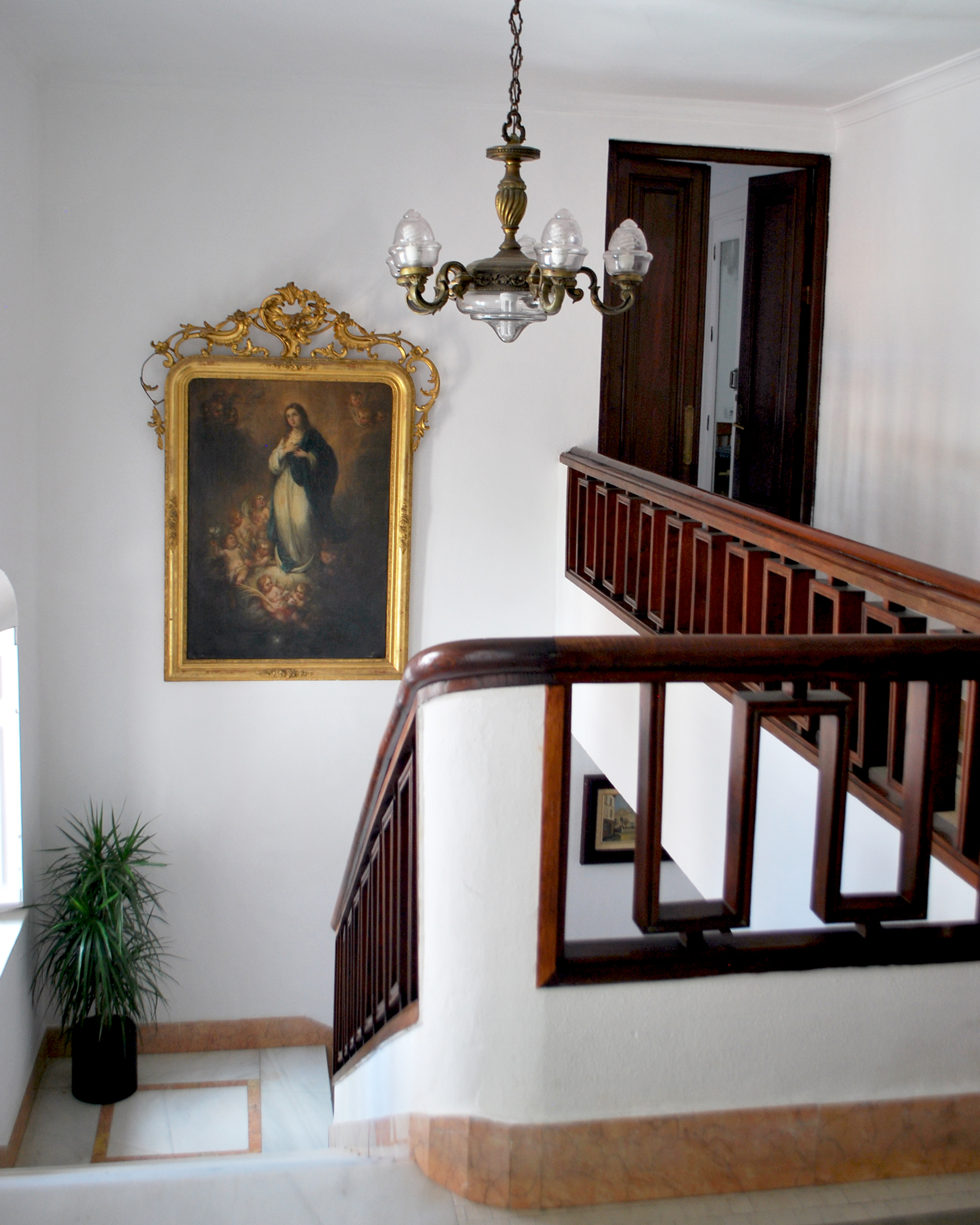 Dark wood banisters and cool marble stairs alongside traditional art and lighting.