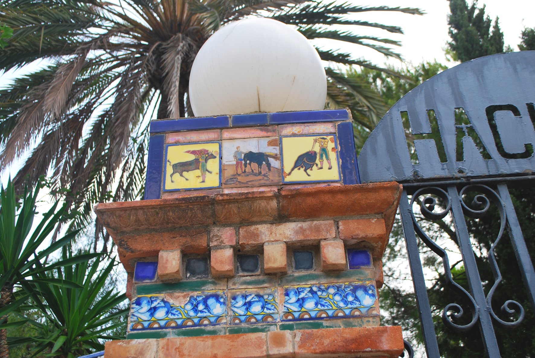 The tiles on the entrance gate pillars tell a story about bull fighting.