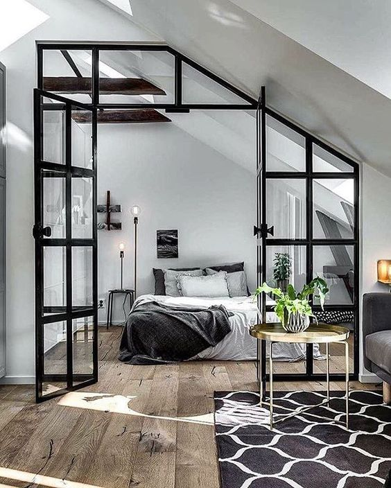 The modern elements like the lighting and the table mix perfectly with the factory-inspired Crittall-style room divider in this Industrial Modern bedroom.
