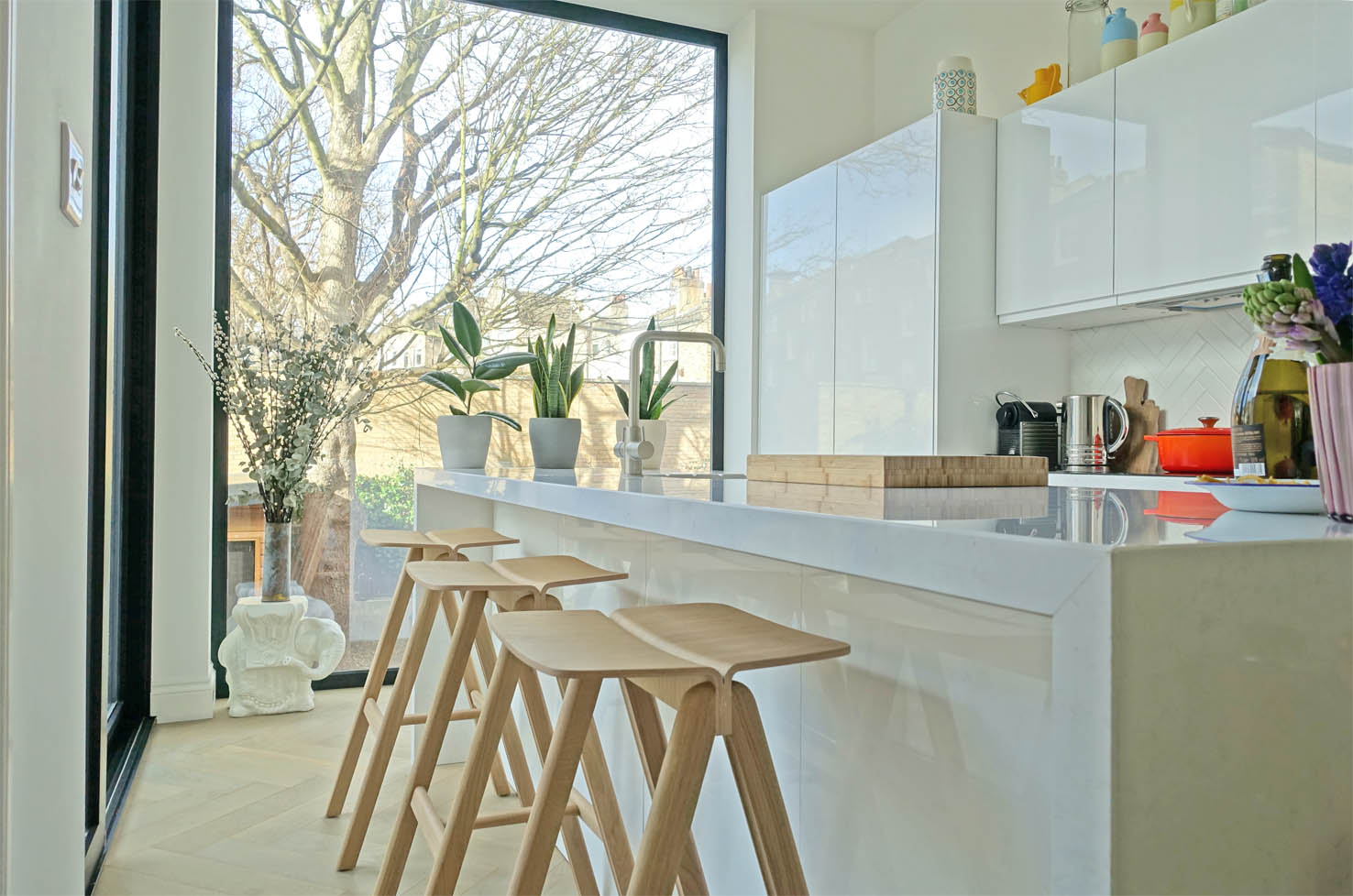The white gloss kitchen is from Magnet and the sisters chose these Hay barstools.