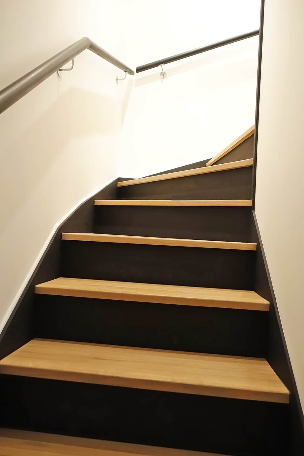 Stylish stairs in black and wood lead down to the three bedrooms and two bathrooms.
