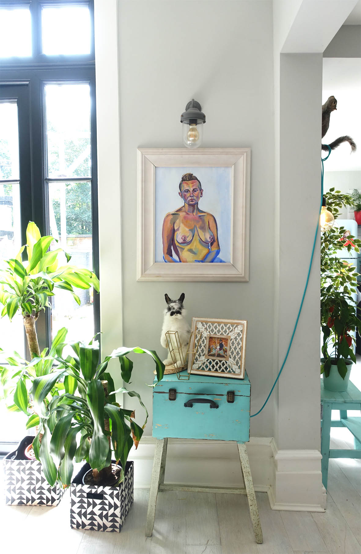 A fabulously styled selection of art, objects, plants and lighting brighten up what would otherwise be a blank, unused area next to the door.