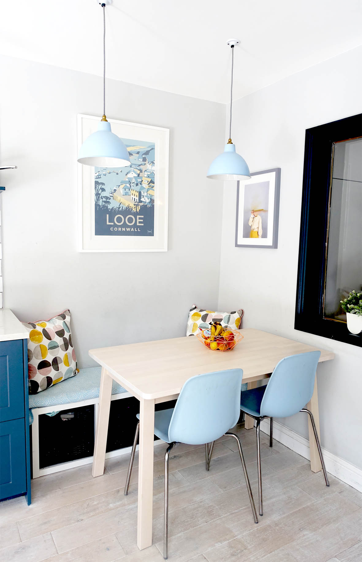 The small dining area is cleverly tucked next to the Kitchen. An Ikea shelf is used on its' side and topped with padding for compact seating.