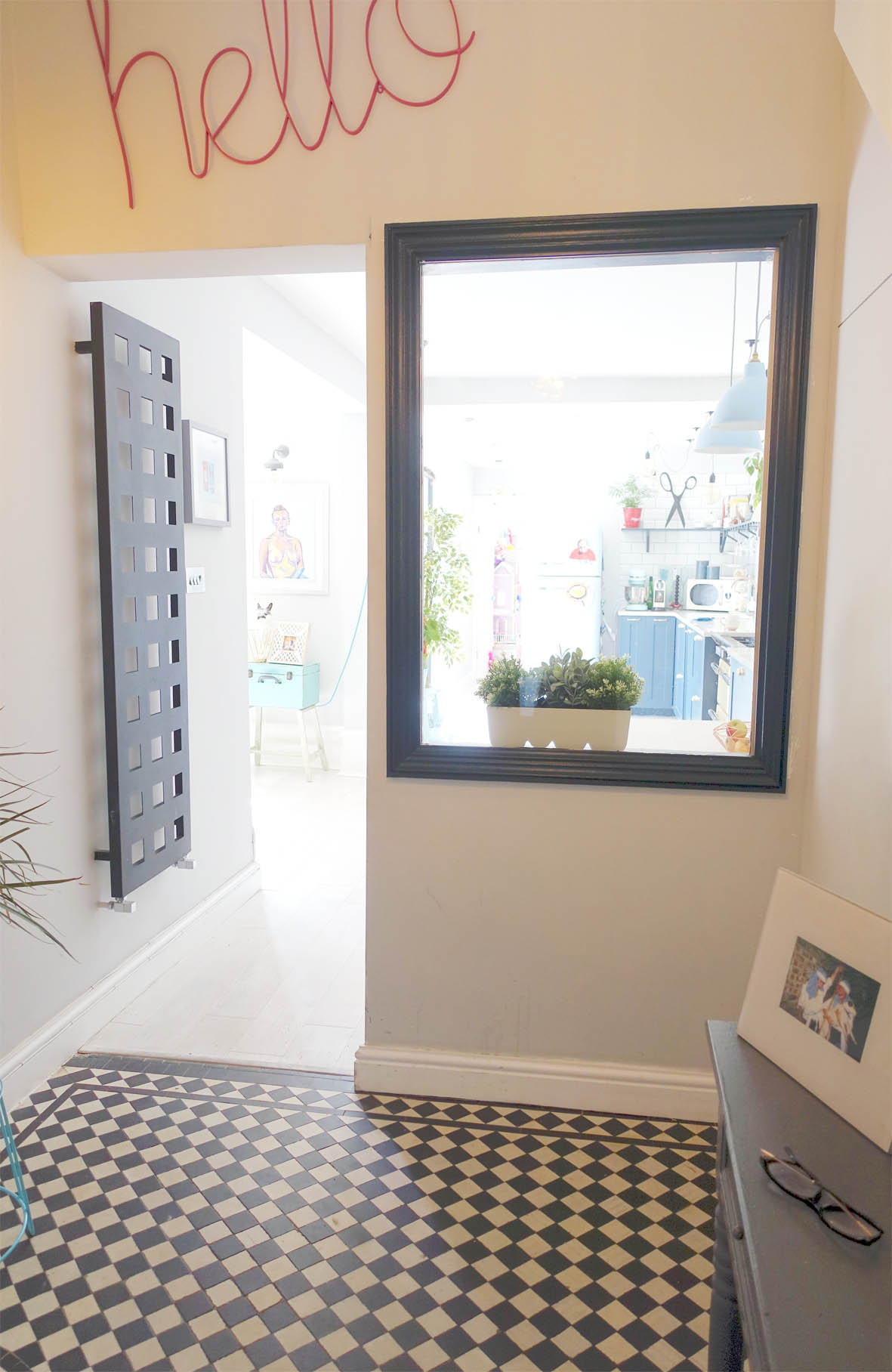 """A bright """"Hello' and original Victorian tiles greet you in the entrance hall where an internal dark-framed window gives a little sneak peek of the vibrant home."""