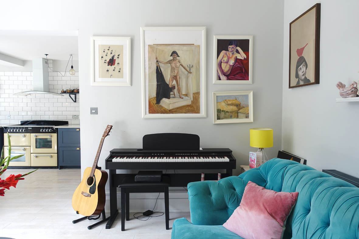 A gloss black piano and a gallery wall in more subdued colours balance out the brighter ones.
