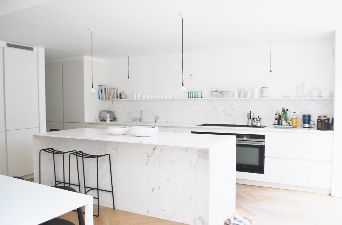 The pale marble encases three sides of the kitchen island.