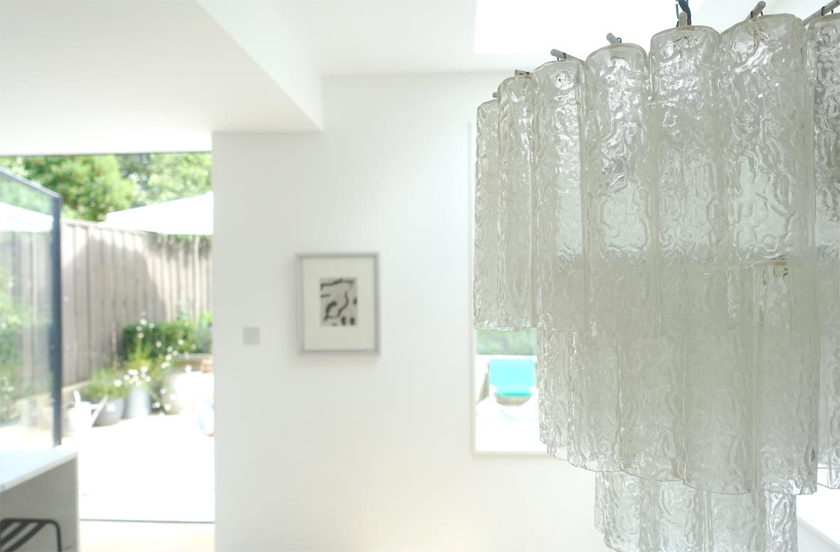 The glass chandelier adds sophisticated texture.
