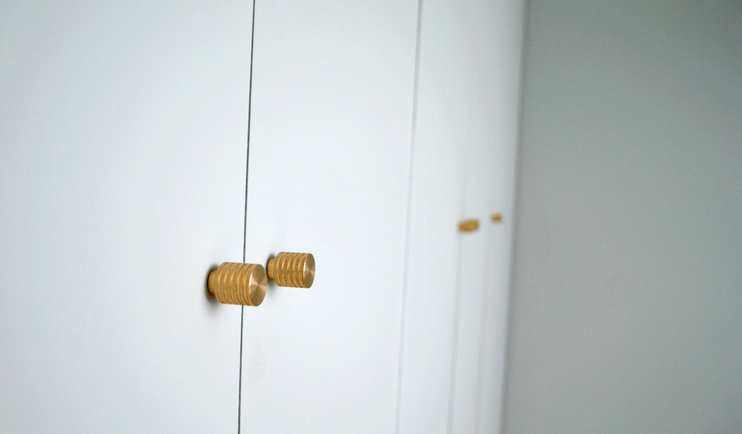 The door knobs are the  Avant Garde Knurled knobs in raw brass  by Dowsing & Reynolds