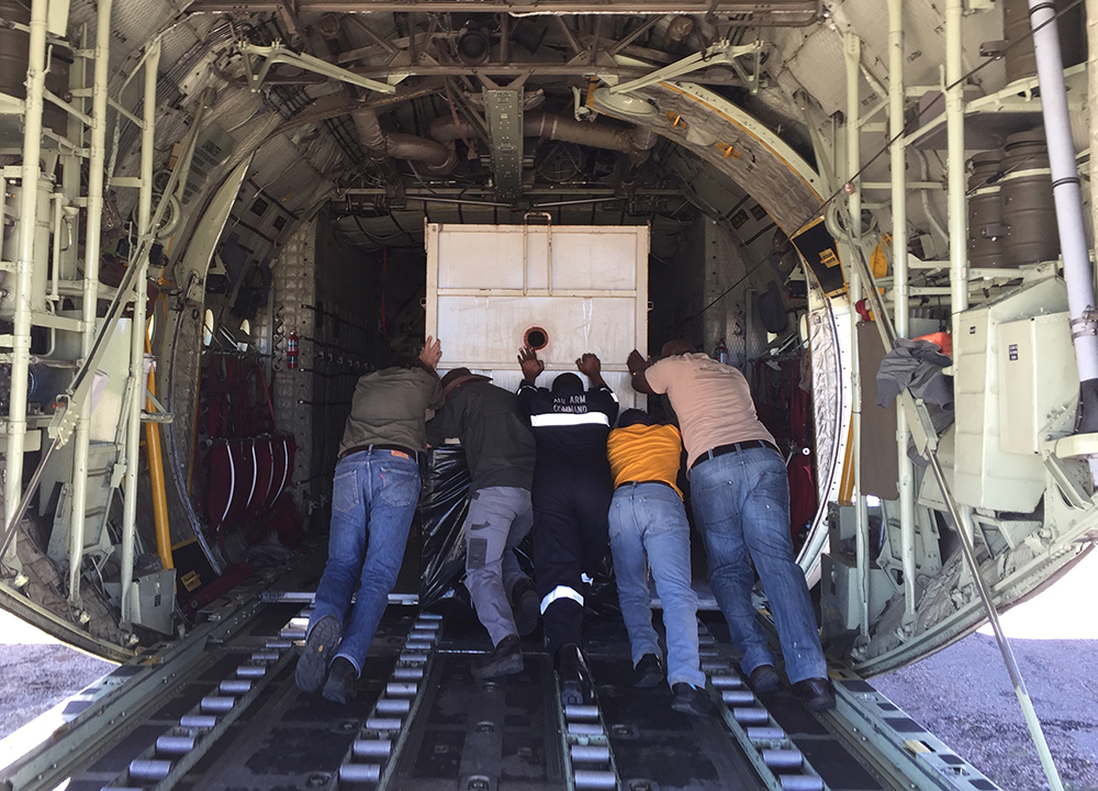 The rhino crates have to be gently loaded into the aircraft. They are very heavy so it's all hands to the pumps!