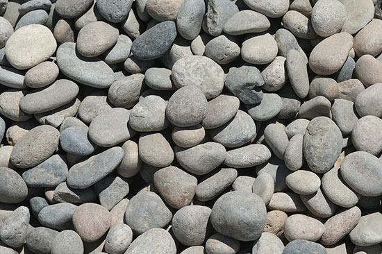 Cobbles (also called River Rock) are a round rock that comes in a variety of sizes. They are often used as a decorative rock in gardens, placed as borders or applied as ground cover.