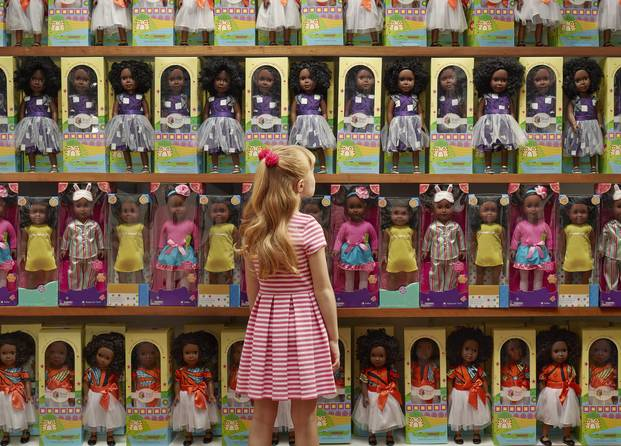 A young white girl looking up at shelves upon shelves of black dolls. Source:Chris Buck/O, the Oprah Magazine