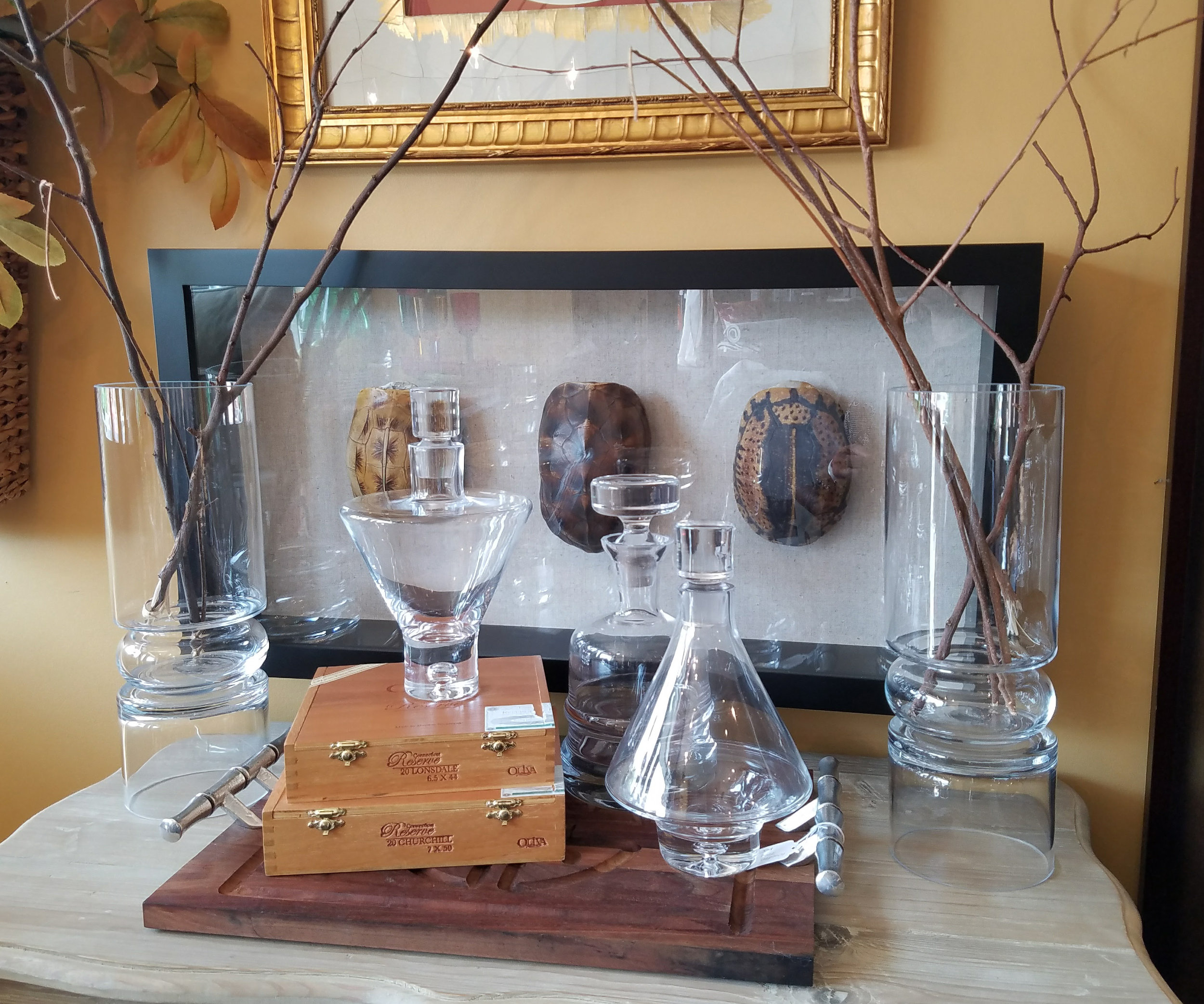 Don't be afraid to add a few decorative touches like framed artwork, cigar boxes, vases, or anything that will pair well with your bar accessories.