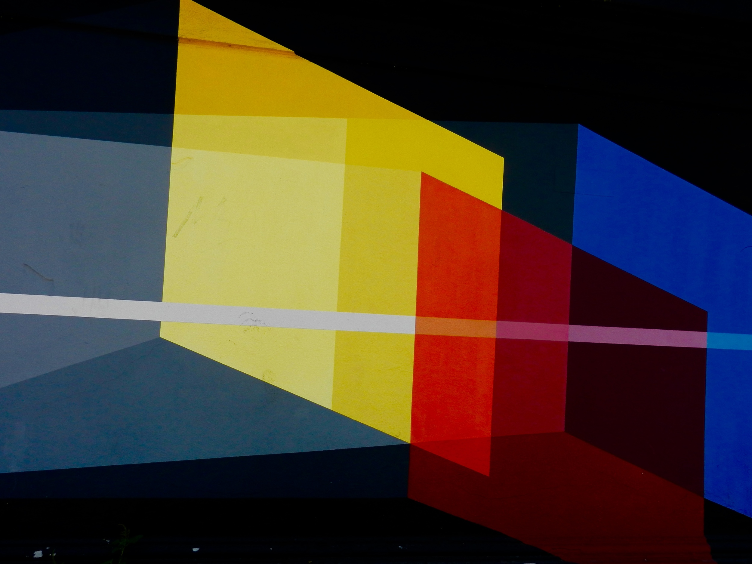 """From Roma Turismo:  """"Derek Bruno installed a mural work curated by Stefano S. Antonelli from 999Contemporary in Testaccio. A seven by four metre work, based on a pure abstract geometric style, where the artist composes using a white line and three squares, from the perspective of the relationship between the objective-subjective, questioning the truth.  The line represents reality, the objective view is on the left, and the subjective on the right, intersecting three """"slices"""" of interaction with reality in basic colours."""""""