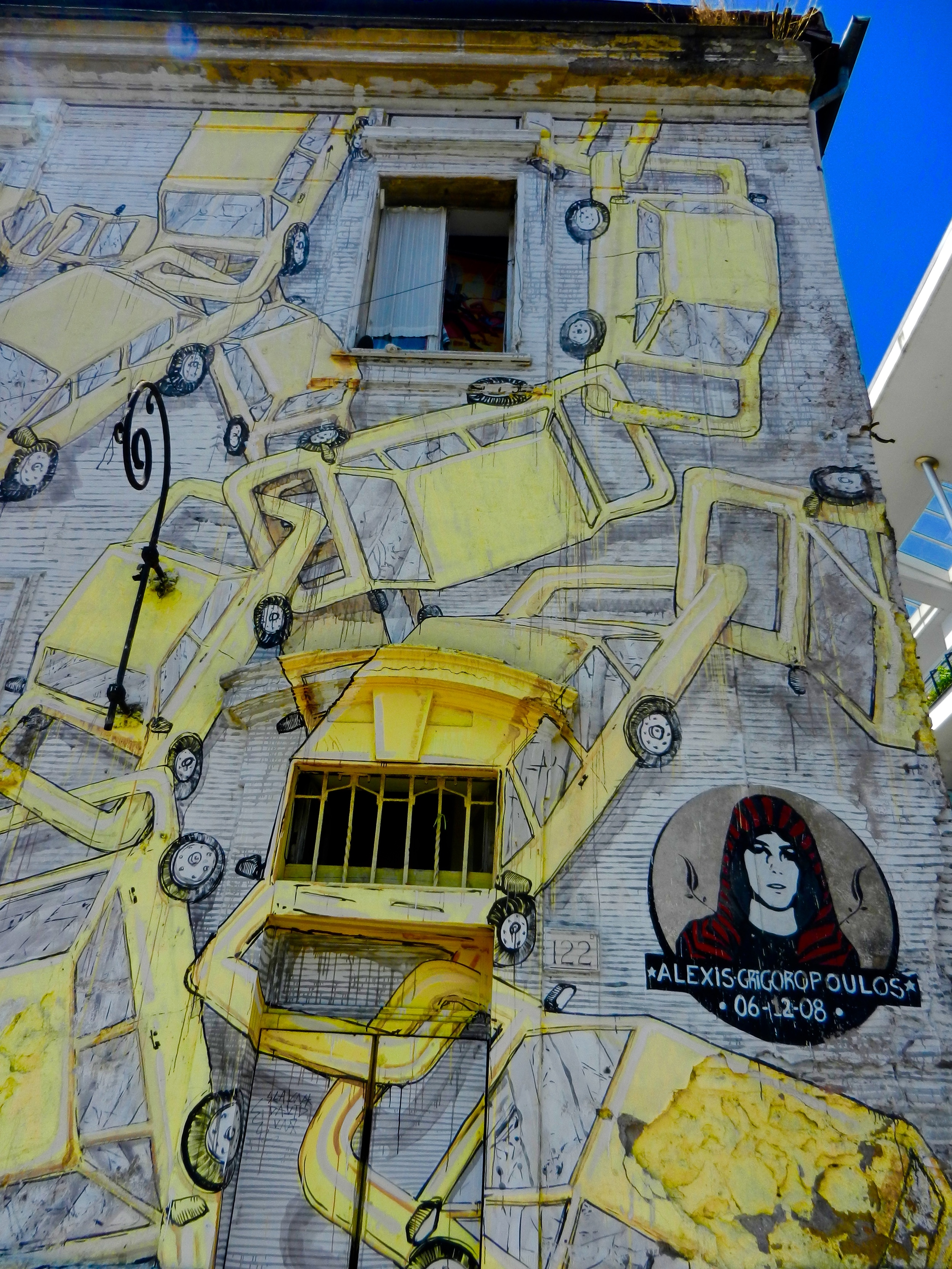 """From Roma Truism:""""  Mural completed by the Blu in February 2013. The artwork represents cars that are chained together and a portrait of Alexis Grigoropoulos, the 15-year old Greek student that was shot on 6 December 2008 by a policeman in Exarchia, the suburb under anarchy in Athens."""""""