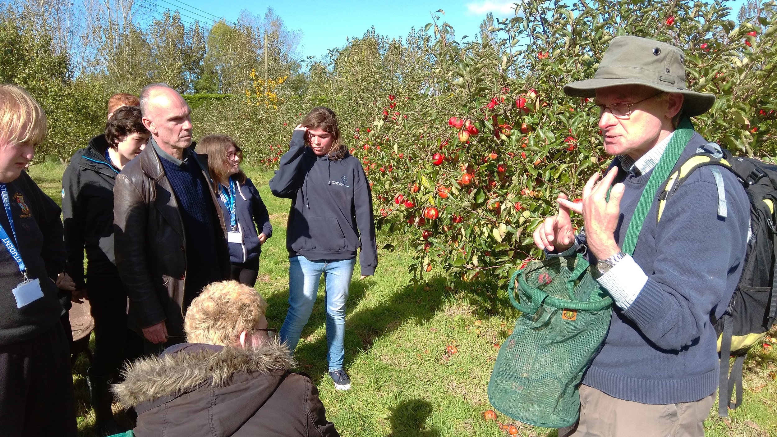 Peter May showing the group how to pick apples