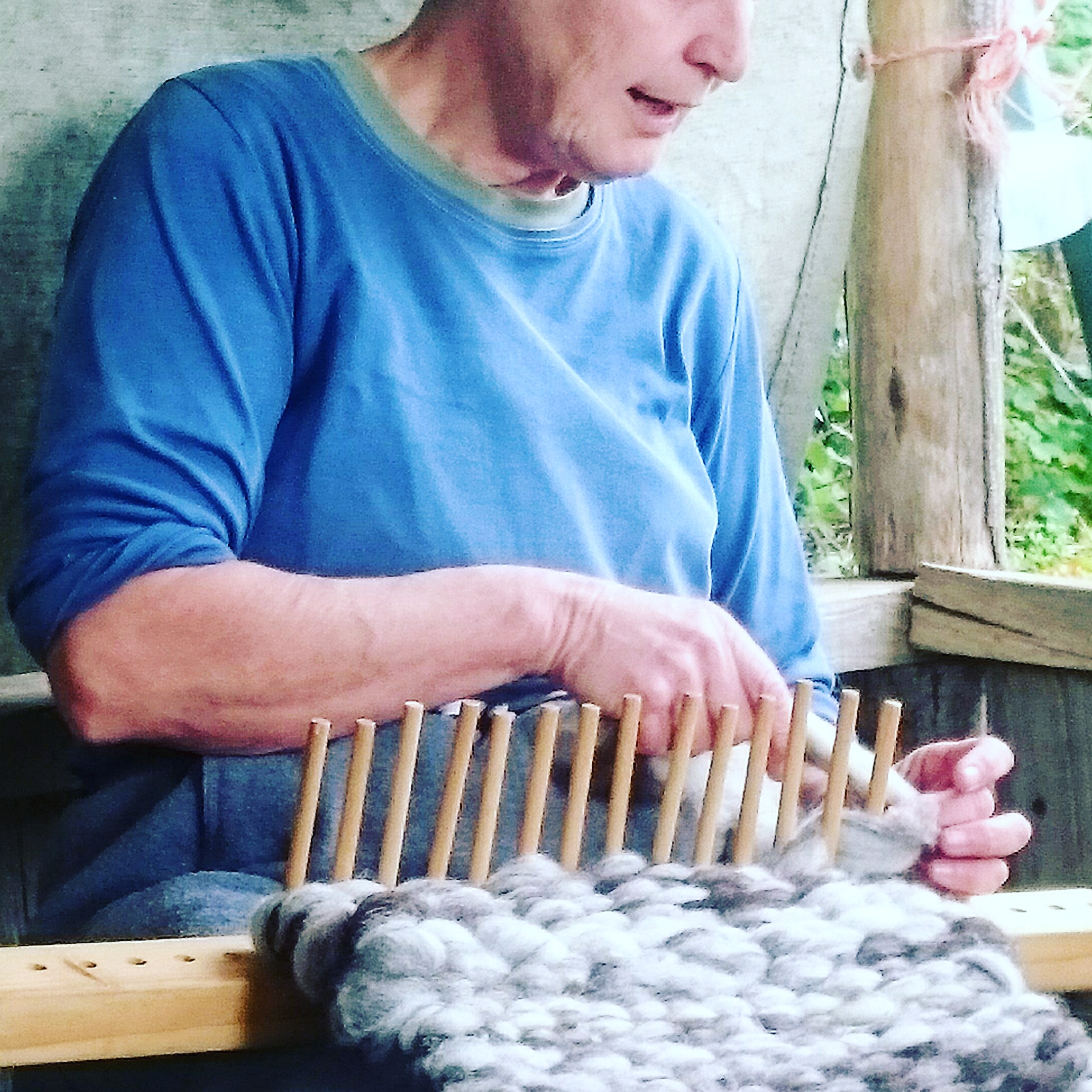 Owena demonstrating peg-loom weaving