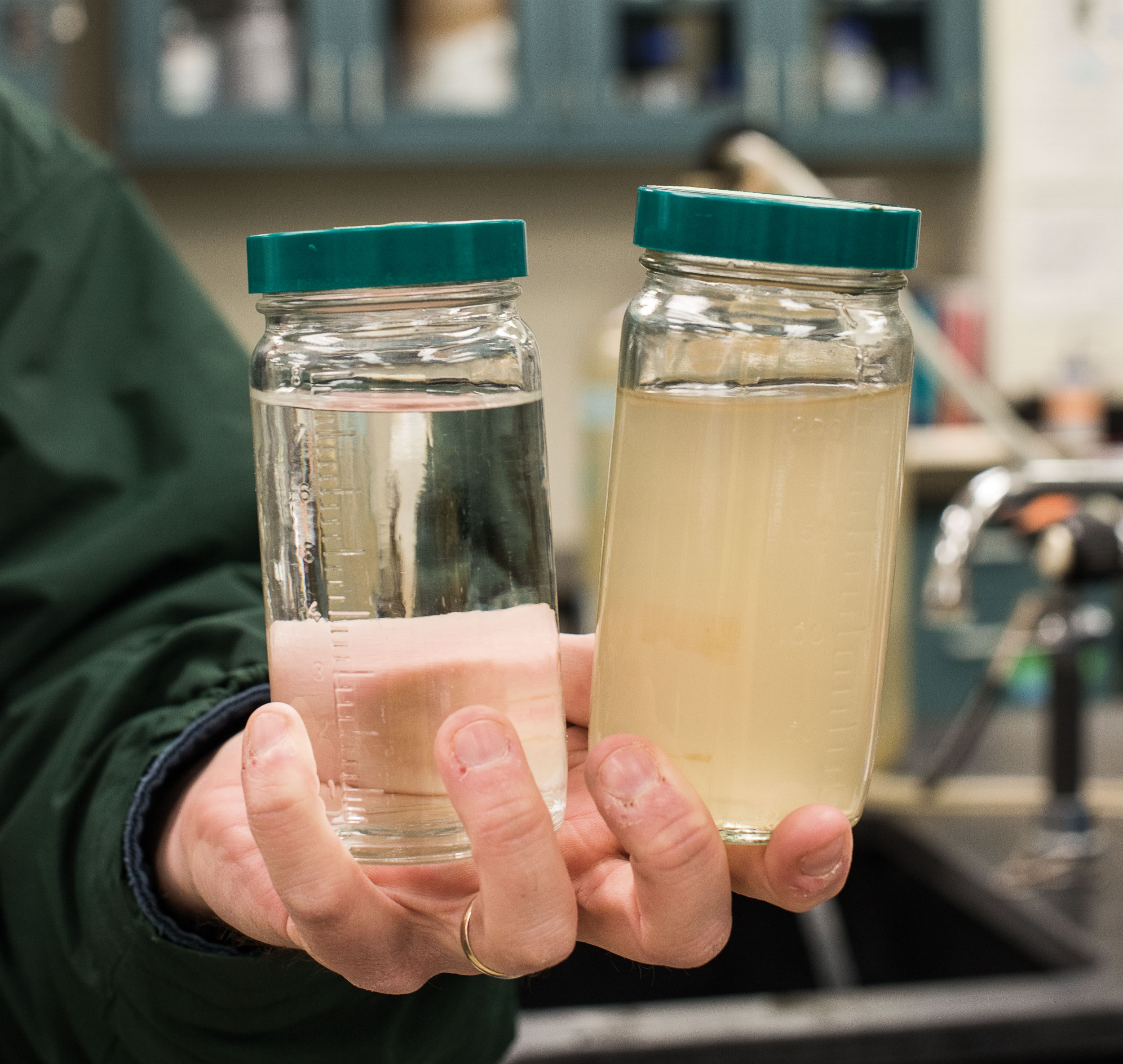 Jeff Swertfeger, who monitors water quality at Greater Cincinnati Water Works, holds water from the Ohio River. Finished water (left) and raw (right).