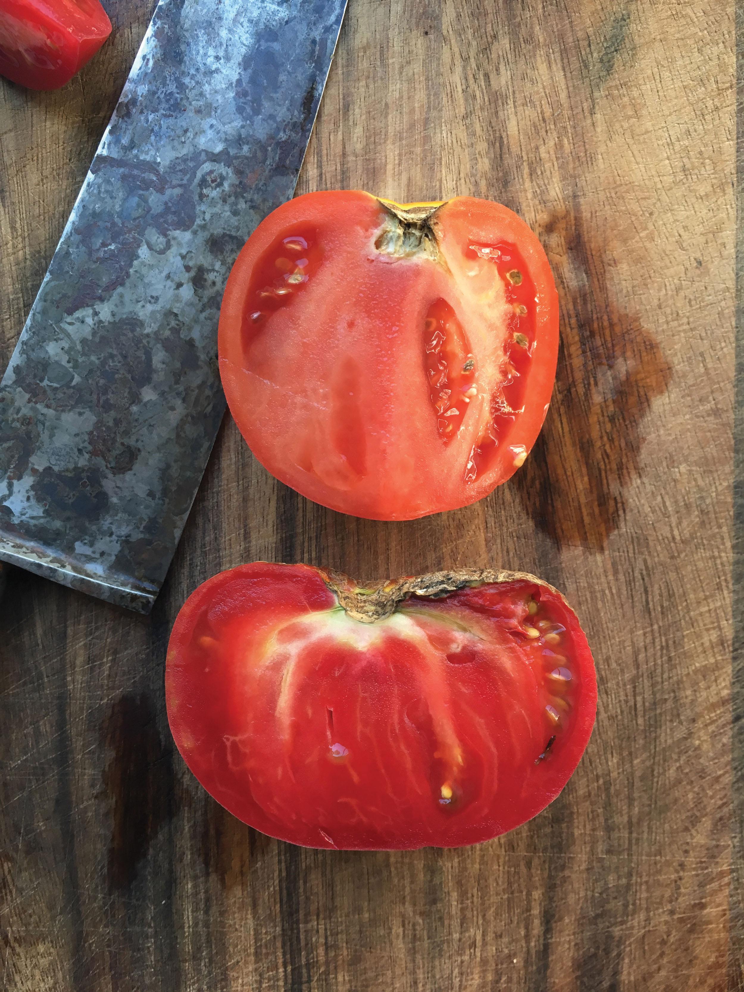 Top: a look inside a conventional tomato. bottom: the deep red sweet pulp of the heirloom fruit Aunt Lou.